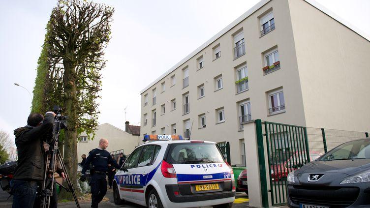 Des policiers devant l'immeuble où a été interpellé un des suspects, à Draveil, dans l'Essonne. (BERTRAND LANGLOIS / AFP)