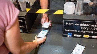 Une personne présente un pass sanitaire, le 16 août 2021 à Perpignan (Pyrénées-Orientales). (ARNAUD LE VU / HANS LUCAS / AFP)