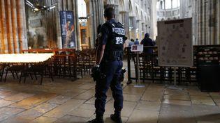 Un policier patrouille au sein de la cathédfrale de Rouen (Seine-Maritime), le 27 juillet 2016. (CHARLY TRIBALLEAU / AFP)