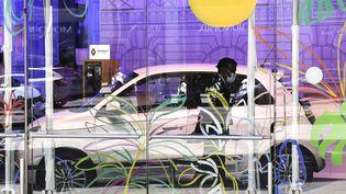 Un homme passe devant une vitrine d'un concessionnaireRenault, à Paris, le 20 mai 2020. (ALAIN JOCARD / AFP)