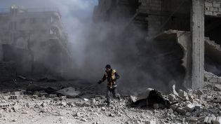 Un secouriste dans les décombres après un raid du régime syrien à Saqba (Syrie), le 23 février 2018. (ABDULMONAM EASSA / AFP)