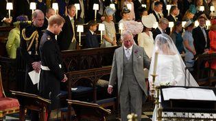 Meghan Markle est conduite à l'autel par le prince Charles sous les yeux de son futur epoux le prince Harry, à la chapelle St George du château de Windsor, le 19 mai 2018. (REUTERS)