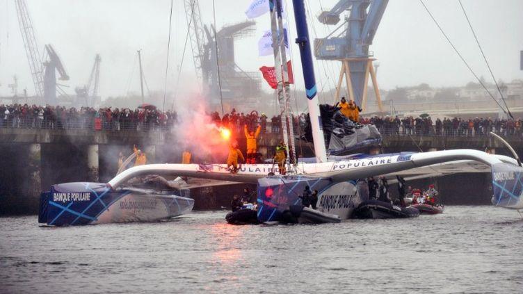 Loïck Peyron et ses co-équipiers saluent la foule venue les acclamer à Brest (Finistère), le 7 janvier 2012. (FRED TANNEAU / AFP)