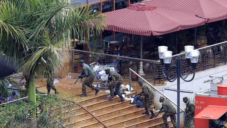 Des soldats kényans prennent d'assaut le centre commercial, le 24 septembre 2013 à Nairobi (Kenya). (NOOR KHAMIS / REUTERS)