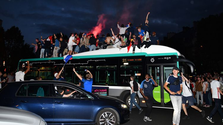 Massés sur un bus, des supporters français fêtent la victoire de la France face à la Belgique, le 10 juillet 2018, à Paris. (MUSTAFA YALCIN / ANADOLU AGENCY / AFP)