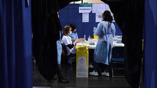 Des membres du personnel médical préparent une dose de vaccin Moderna Covid-19 dans un centre de vaccination Covid-19 installé dans le vélodrome national de Saint-Quentin-en-Yvelines, au sud-ouest de Paris, le 23 mars 2021. (ALAIN JOCARD / AFP)