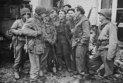 Militaires de la 9e armée américaine (portant des casques) discutent avec des militaires canadiens à Geldern (Rhénanie du Nord-Westphalie) le 3 mars 1945. (AFP - COLL-DITE - PHOTO12)