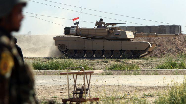 Un char irakien roule dans un champ situé à l'ouest de Tikrit (Irak), le 11 mars 2015, au cours d'une opération lancée pour reprendre la ville aux jihadistes de l'Etat islamique. (AHMAD AL-RUBAYE / AFP)