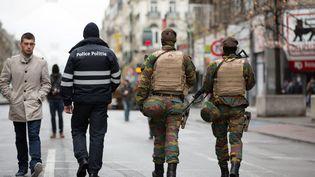 Un policier et des militaires patrouillent dans les rues de Bruxelles (Belgique), le 22 novembre 2015. (OCTAVIAN CARARE / MAXPPP)