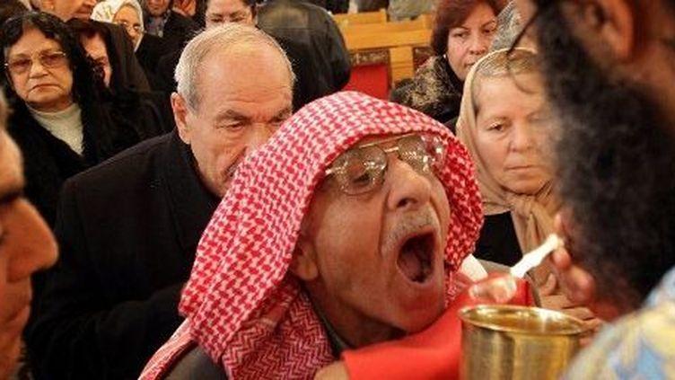 Un chrétien de Syrie reçoit la communion lors de la messe de célébration de l'Epiphanie à l'église de Damas, le 6 janvier 2011. (AFP PHOTO/ LOUAI BESHARA )
