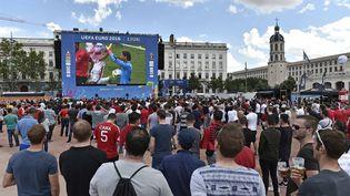 """Des supporters regardent un match de l'Euro dans la """"fan zone"""" de Bellecour, à Lyon (Rhône), le 11 juin 2016. (MAXPPP)"""