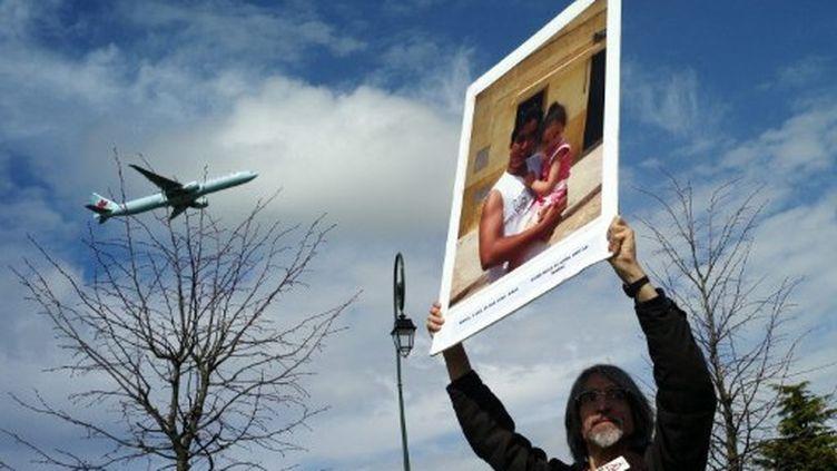 Un manifestant brandit un poster d'une personne expulsée lors d'un rassemblement le 29 mars 2010 à l'appel d'une quinzaine d'associations près du nouveau centre de rétention administrative du Mesnil-Amelot (AFP)