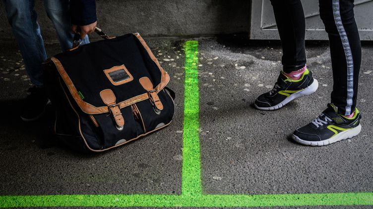 Un marquage au sol vert indique aux écoliersla distance à respecter, le 12 mai 2020, à Paris. (PHILIPPE LOPEZ / AFP)
