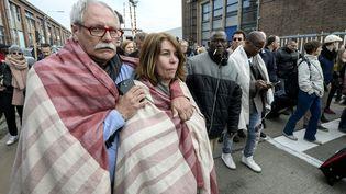 Des passagers évacuent l'aéroport international de Bruxelles (Belgique), le 22 mars 2016. (DIRK WAEM / BELGA / AFP)