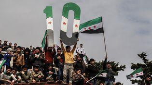 Des Syriens commémorent le dixième anniversaire du début de la guerre en Syrie, à Idlib, le 15 mars 2021. (MUHAMMED ABDULLAH / ANADOLU AGENCY / AFP)