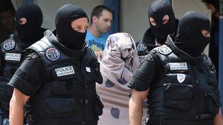 Une femme escortée par les forces de l'ordre à la sortie de l'immeuble où vit le suspect de l'attentat de l'Isère, Yassin Salhi, à Saint-Priest (Rhône), le 26 juin 2015. (PHILIPPE DESMAZES / AFP)