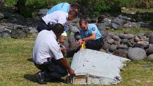 Des gendarmes et des policiers inspectent, mercredi 29 juillet, le fragment d'aile découvert à La Réunion. (  REUTERS)