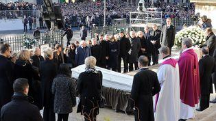Le cerceuil sur les marches de la Madeleine, entouré par la famille, des religieux et Emmanuel Macron  (Ludovic Marin / AFP)