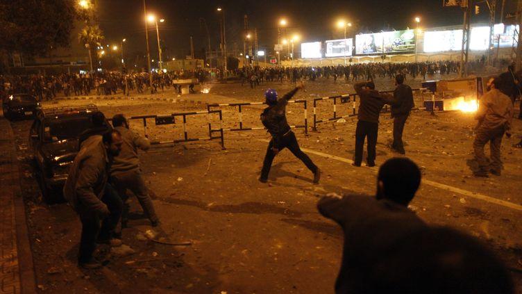 Opposants et partisans du chef de l'Etat égyptien Mohamed Morsi s'affrontent près du palais présidentiel, le 5 décembre 2012 au Caire (Egypte). (MAHMOUD KHALED / AFP)