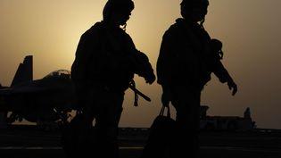 """Des pilotes de chasse américains, le 10 août 2014, sur le pont du porte-avion """"George H.W. Bush"""", stationné dans le golfe persique. (HASAN JAMALI / AP / SIPA)"""