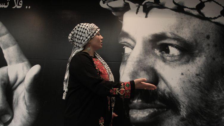 Une femme palestienne passe devant une image de Yasser Arafat, le 10 novembre 2013, à Ramallah. ( MAXPPP)