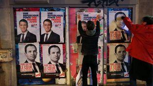 Un militant soutient à l'ancien Premier ministre et candidat à la primaire de la gauche Manuel Valls, colle une affiche sur celle d'un autre candidat de la gauche Benoit Hamon. Paris, le 11 janvier 2017. (JACQUES DEMARTHON / AFP)