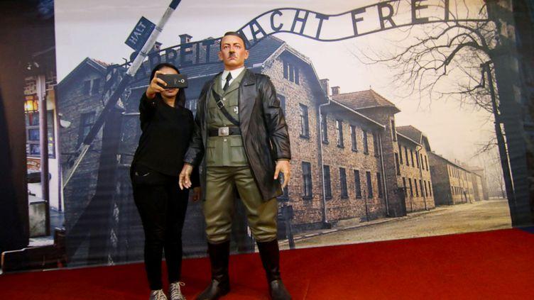 Une touriste seprend en photo avec la statue de cire d'Hitler, proposée parun musée de Yogyakarta, en Indonésie, le 10 novembre 2017. (HENRYANTO / AFP)