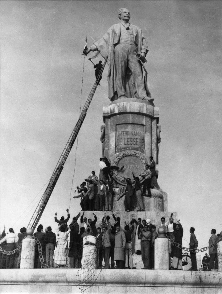 Photo du 30 décembre 1956montrant un Egyptien tentant d'atteindre un drapeau français sur la statue de Lesseps en Egypte. (AFP)