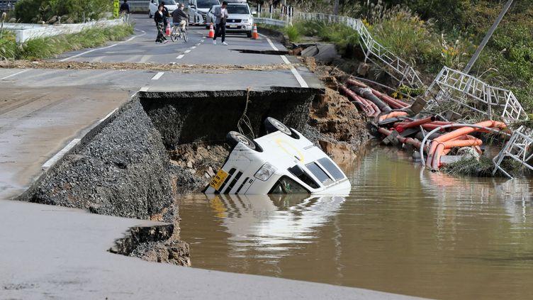 Un véhicule est renversé dans un ravin formé par l'effondrement d'une route lors du typhon Hagibis, le 14 octobre 2019, à Mito City (Japon). (KOICHI NALAMURA / YOMIURI / AFP)