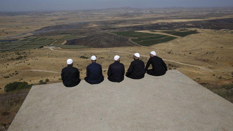 Des Druzes sur les hauteurs du Golan, annexées par les Israéliens, regardent la province de Quneitra, dans le sud-ouest de la Syrie, de l'autre côté de la frontière, le 7 juillet 2018. (JALAA MAREY / AFP)