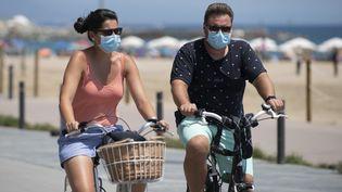 Un couple de cyclistes le long de la plage à Barcelone(Espagne), le 18 juillet 2020. (JOSEP LAGO / AFP)