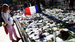 Une femme se recueille devant le mémorial aux victimes de l'attentat de la promenade des Anglais, à Nice, le 16 juillet 2016. (GIUSEPPE CACACE / AFP)