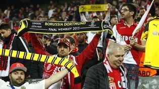Des supporters monégasques exhibent des écharpes en solidarité avec le Borussia Dortmund, après les explosions visant le bus de l'équipe allemande,le 11 avril 2017. (ODD ANDERSEN / AFP)