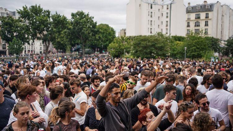 Des fêtards dansent au Jardin Villemin, dans le 10e arrondissement de Paris, le 21 juin. (ABDULMONAM EASSA / AFP)