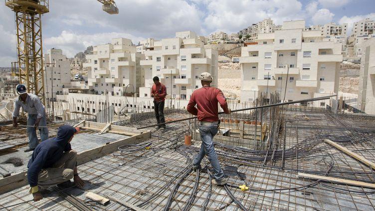 Des ouvriers palestiniens travaillent sur un chantier dans une colonie israélienne de Jérusalem-Est, le 23 avril 2010. (AHMAD GHARABLI / AFP)