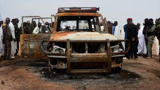 Des officiels du Niger près de la voiture de six humanitaires français et de deux Nigériens travaillant pour l'ONG Acted, tués dans une attaque au sein de la réserve de Kouré (Niger), le 9 août 2020. (BOUREIMA HAMA / AFP)