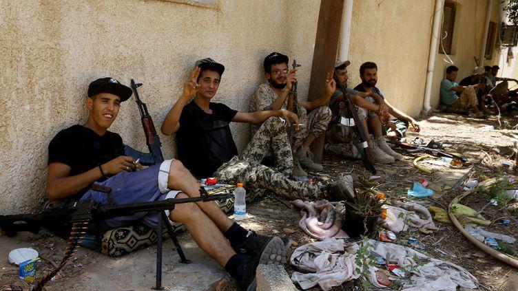 Des combattants fidèles au Gouvernement d'accord national (GNA) de Fayez al-Sarraj, reconnu internationalement, se reposent entre deux affrontements avec les forces fidèles à l'homme fort de l'Est, Khalifa Haftar, le 19 juin 2019dans la région d'al-Sawani, au sud de Tripoli. (MAHMUD TURKIA / AFP)
