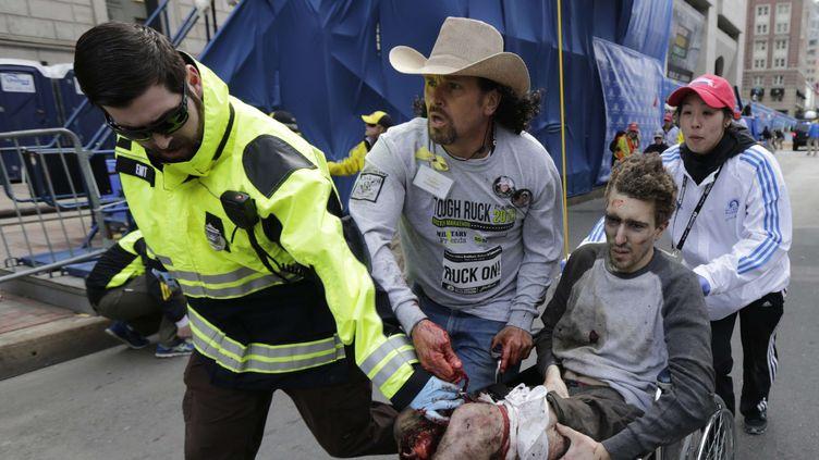 Des secouristes, dont Carlos Arredondo (au centre), évacuent un homme grièvement blessé par le double attentat qui a frappé le marathon de Boston (Etats-Unis), le 15 avril 2013. (CHARLES KRUPA / AP/ SIPA)