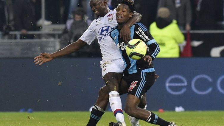 Le défenseur lyonnais Mapou Yanga-Mbiwa à la lutte avec l'attaquant de l'OM Michy Batshuayi (PHILIPPE DESMAZES / AFP)