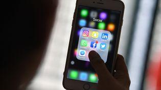 Des applications de réseaux sociaux sur un smartphone (illustration). (MANAN VATSYAYANA / AFP)