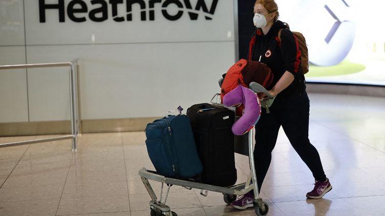 Une passagère portant un masque FFP2 lors de son arrivée au terminal 2 de l'aéroport international d'Heathrow à Londres (Angleterre), le 24 février 2021. (TOLGA AKMEN / AFP)