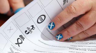 Une personne s'occupe du dépouillement des bulletins lors des législatives britanniques à Aberdeen (Ecosse), le7 mai 2015. (CATHAL MCNAUGHTON / REUTERS )
