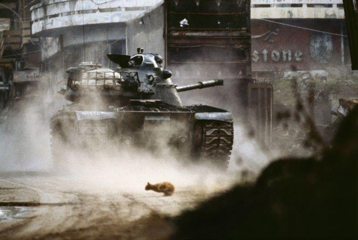 Liban, 1984. Beyrouth. Un char de l'armée libanaise chrétienne tire sur les milices musulmanes dans le centre-ville. Un chat de religion indéterminée fuit les combats. (Patrick Chauvel)