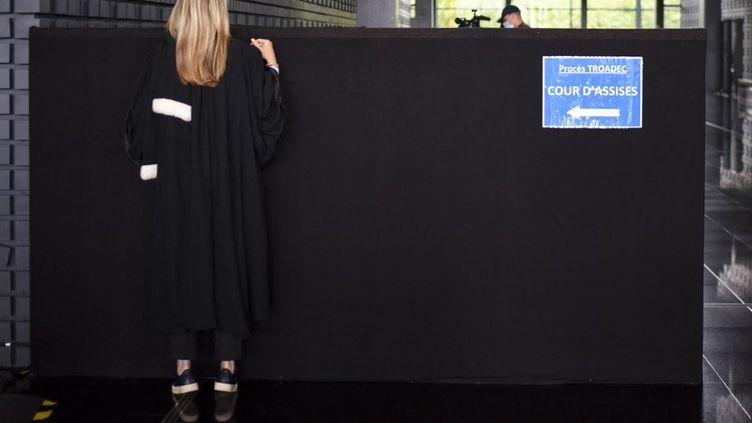 Une avocate regarde par dessus un panneau indiquant le chemin de la cour d'assises au palais de justice de Nantes, le 23 juin 2021, au deuxième jour du procès de l'affaire Troadec. (SEBASTIEN SALOM-GOMIS / AFP)