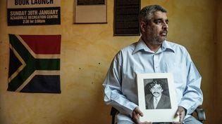 Imtiaz Cajee, neveu d'Ahmed Timol, avec une photo de son oncle, mort en octobre 1971 pendant le régime de l'apartheid, le 25 mai 2017 à Prétoria (Afrique du Sud). (GIANLUIGI GUERCIA / AFP)