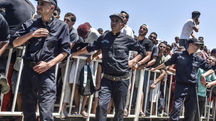 De jeunes Algériens font la queue devant un stade, le 16 juillet 2019, pour acheter des billets d'avion pour Le Caire afin de soutenir leur équipe lors de la finale de la CAN 2019, le 19 juillet, entre l'Algérie et le Sénégal. (RYAD KRAMDI / AFP)