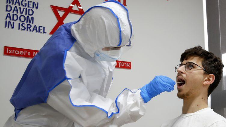 Un agent des services paramédicaux israéliens réalise un test de contamination au coronavirus au centre national des opérations, à Kiryat Ono, près de Tel-Aviv. (JACK GUEZ / AFP)
