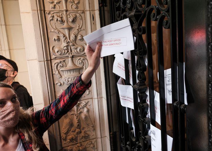 """Une manifestante glisse une enveloppe marquée de l'inscription """"Sauvez la poste, sauvez la démocratie"""" dans la porte du patron de la poste américaine, Louis DeJoy, le 15 août 2020 à Washington. (MICHAEL A. MCCOY / GETTY IMAGES NORTH AMERICA)"""