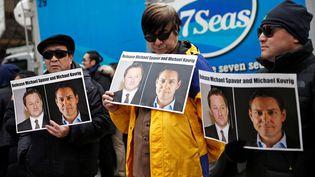 Des manifestants portant des pancartes appelant à la libération de Michael Spavor et de Michael Kovrig, à Vancouver au Canada, le 6 mars 2019. (LINDSEY WASSON / REUTERS)