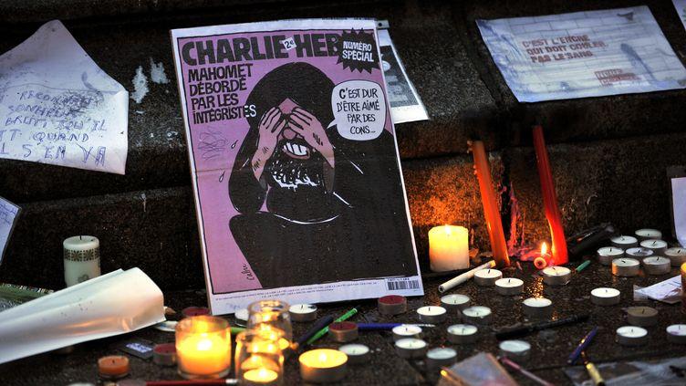 Le numéro de Charlie Hebdo, qui lui avait valu un procès en raison de la caricature de Mahomet, est posé en hommage aux victimes de l'attentat qui a frappé la rédaction, le 7 janvier 2015. (ALAIN LE BOT / PHOTONONSTOP / AFP)